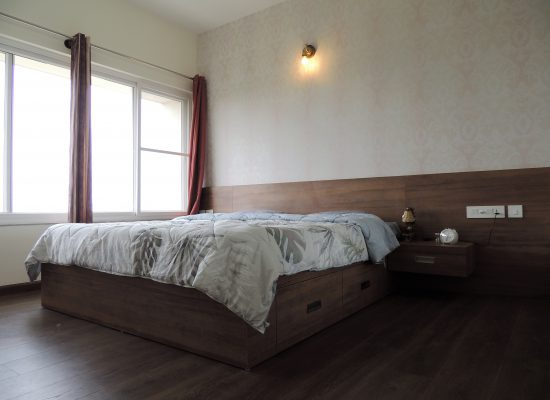 master bedroom with wooden flooring and back panel